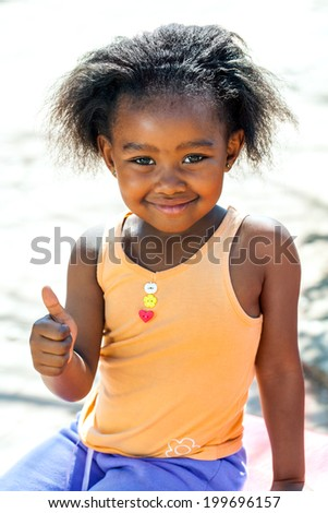Outdoor portrait of cute African girl doing thumbs up sign. - stock photo