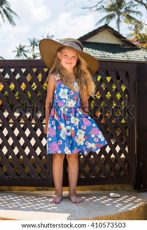 Outdoor portrait of cute little girl in blue floral dress and big beach straw hat. Beautiful lady smile to the camera. Summer sunny day. House with wooden fence at tropical background. Mothers day. - stock photo