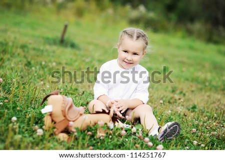 Outdoor portrait of cute little girl sitting on grass and playing with toys - stock photo