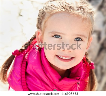 Outdoor portrait  of cute sitting little girl in spring day - stock photo