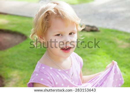 Outdoor portrait of cute smiling Caucasian blond baby girl in a summer park - stock photo