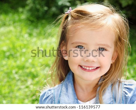 Outdoor portrait of cute smiling little girl - stock photo