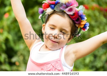 Outdoor portrait of expressive beautiful little girl wearing flower wreath posing with hands raised up - stock photo