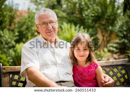 Outdoor portrait of grandchild embracing grandfather - stock photo