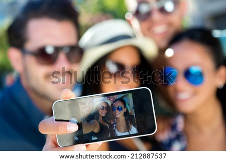 Outdoor portrait of group friends taking photos with a smart phone. - stock photo