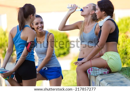 Outdoor portrait of group of young women doing stretching in the park. - stock photo