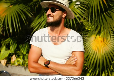 Outdoor portrait of handsome man posing outdoor with straw hat,boho style handwatch,street fashion style,classic suit,hiker man,man's fashion,urban street style,toned body,glowing skin,male accessory - stock photo