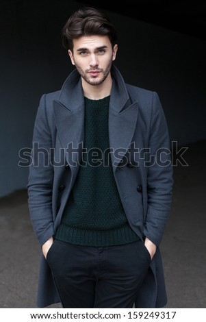 Outdoor portrait of handsome young man in coat - stock photo
