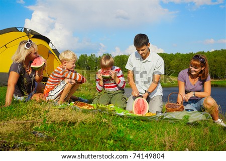 outdoor portrait of happy families at the picnic eating watermelon - stock photo