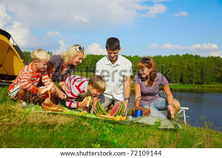 outdoor portrait of happy families at the picnic, going to eat watermelon cut in two halfs. - stock photo