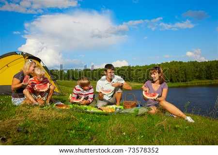 outdoor portrait of happy families enjoying watermelon at the picnic near camp tent - stock photo