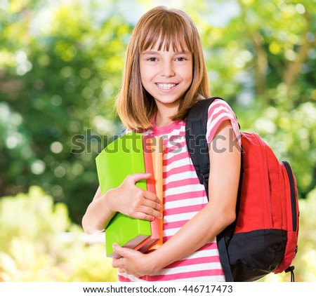 Outdoor portrait of happy girl 10-11 year old with books. Back to school concept. - stock photo