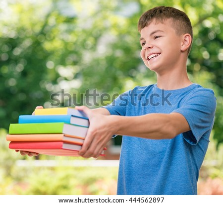 Outdoor portrait of happy teen boy 12-14 year old with books. Back to school concept. - stock photo