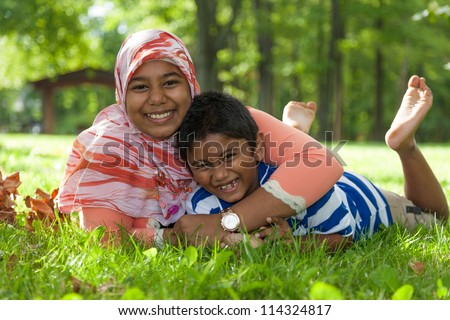 Outdoor portrait of indian brother and sister playing - stock photo