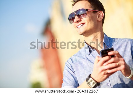 Outdoor portrait of man with mobile phone in the street. - stock photo