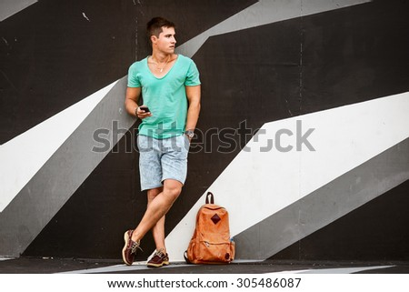 Outdoor portrait of modern young man with mobile phone and bag near wall - stock photo