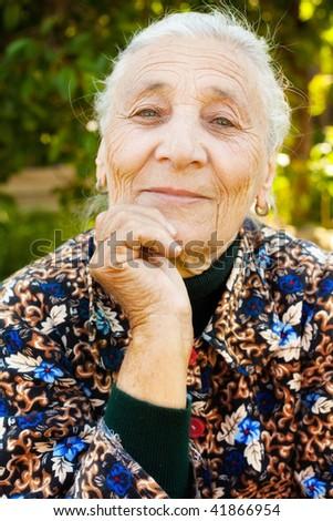 Outdoor portrait of one elegant senior lady - stock photo