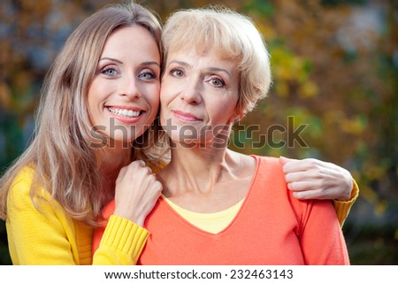 Outdoor portrait of pretty middle aged caucasian mother with her smiling adult daughter looking at the camera in the garden - stock photo