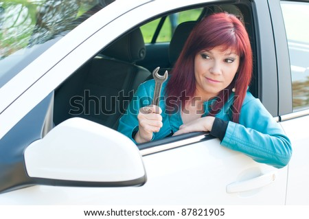 Outdoor portrait of puzzled red-haired young woman sitting in her car with a screw key - stock photo