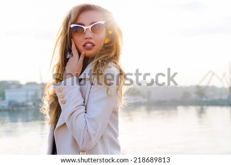 Outdoor portrait of seductive beautiful woman with full sexy lips, blonde curled ombre hairs,  luxury stylish golden cat eye sunglasses, posing at sea port. fashion fall shot. Romantic mood. - stock photo