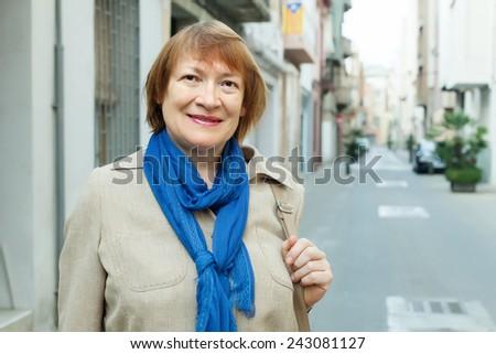 Outdoor portrait of  senior woman at european town street - stock photo