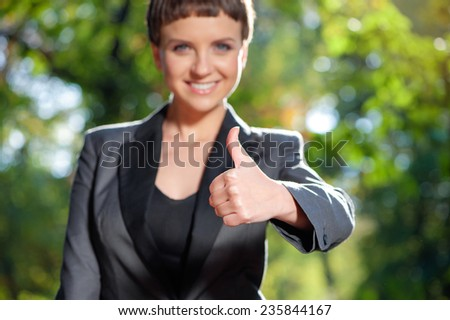 Outdoor Portrait of smiling businesswoman holding thumb up with focus on thumb - stock photo
