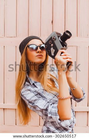 Outdoor portrait of stylish photographer girl holding vintage retro camera,wearing bright trendy sunglasses and jacket,amazing view of city from the roof.Toned,lifestyle,accessorize,hiker - stock photo