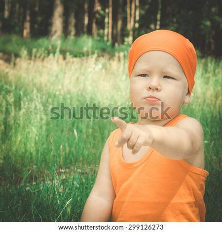 Outdoor portrait of the cute baby pointing - stock photo