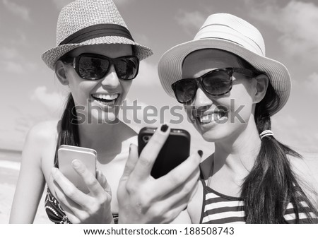 Outdoor portrait of two friends taking photos with a smart phone.  - stock photo