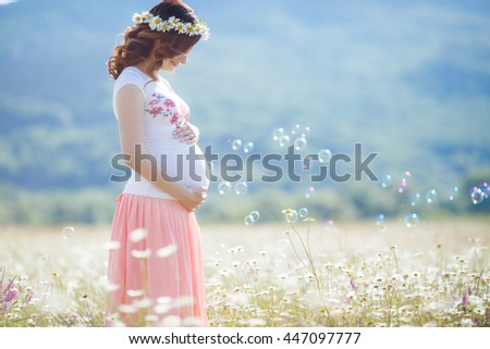Outdoor portrait of unrecognizable young pregnant woman in the field. beautiful pregnant woman in wreath relaxing in the summer nature meadow. pregnant woman relaxing in flowers - stock photo