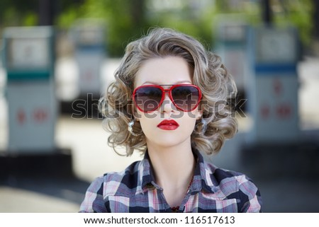 outdoor portrait of young beautiful blonde woman posing on gas station with a lot of gas pumps on background - stock photo