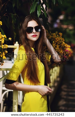 Outdoor portrait of young beautiful fashionable lady posing on street. Model wearing sunglasses & stylish yellow summer dress. Girl looking at camera. Female fashion concept. City lifestyle. Sunny day - stock photo