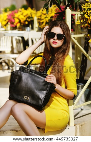 Outdoor portrait of young beautiful fashionable lady posing on the street. Model wearing sunglasses & stylish summer dress. Girl looking at camera. Female fashion concept. City lifestyle. Sunny day - stock photo