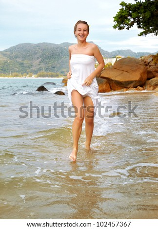 outdoor portrait of young beautiful girl in white cotton clothes running in azure waters of of Phuket island, Thailand - stock photo