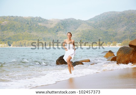 outdoor portrait of young beautiful girl in white cotton clothes running in azure waves of of Phuket island, Thailand - stock photo