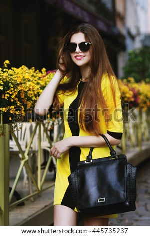 Outdoor portrait of young beautiful happy smiling lady walking on street. Model wearing sunglasses & stylish summer dress. Girl looking at camera. Female fashion concept. City lifestyle. Sunny day  - stock photo