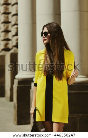 Outdoor portrait of young beautiful lady walking on the street. Model wearing sunglasses & stylish yellow summer dress. Girl looking aside. Female fashion. City lifestyle. Sunny day. Waist up. Toned - stock photo