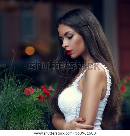 Outdoor portrait of young beautiful stylish woman with long dark hair and red lips posing in white lace top. Art fashion portrait of pensive or thoughtful girl with shallow depth of field - stock photo