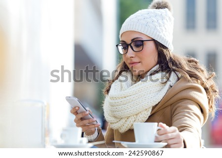 Outdoor portrait of young beautiful woman using her mobile phone in a cafe. - stock photo