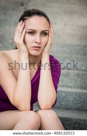 Outdoor portrait of young beautiful worried woman sitting on stairs - stock photo