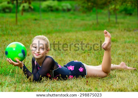 outdoor portrait of young cute little girl gymnast training with ball on grass - stock photo