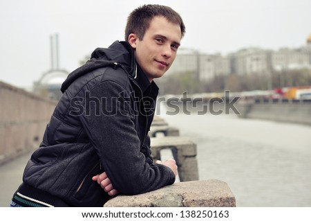 Outdoor portrait of young handsome man near river - stock photo