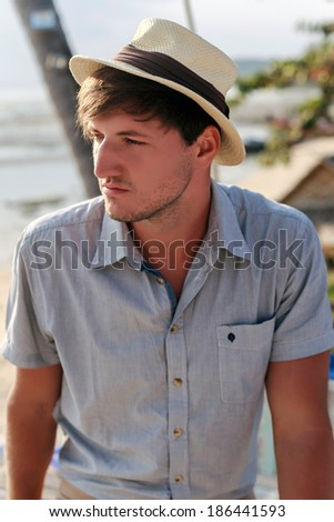 Outdoor portrait of young handsome man posing outdoor in in summer sun light wearing stylish retro hat. Warm sunshine colors. - stock photo