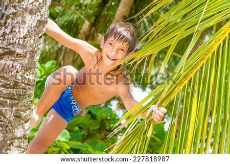outdoor portrait of young happy child boy in tropical background with palm trees - stock photo