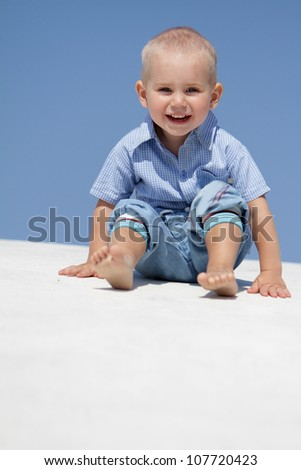 outdoor portrait of young happy child on blue sky background - stock photo