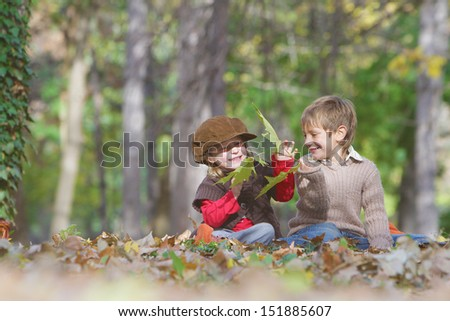 outdoor portrait of young happy children girl and boy on autumn forest background - stock photo