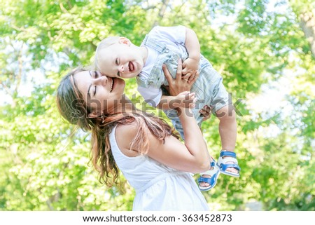 outdoor portrait of young happy smiling mother with her baby son having fun on natural background - stock photo