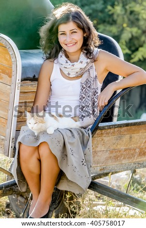 outdoor portrait of young happy woman with cat on natural background on farm - stock photo