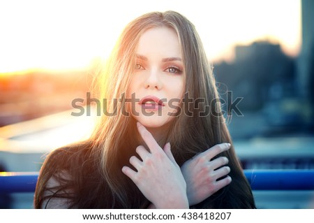 Outdoor portrait of young pretty sexy woman with magic eyes posing at roof at the end of bright sunset. Lovely soft back light.  - stock photo