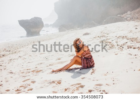 Outdoor portrait of young pretty woman posing near the sea alone and waiting for her sailor man husband in sunglasses sitting on a white beach in Bali, Indonesia with a tan leather fashion clothing  - stock photo